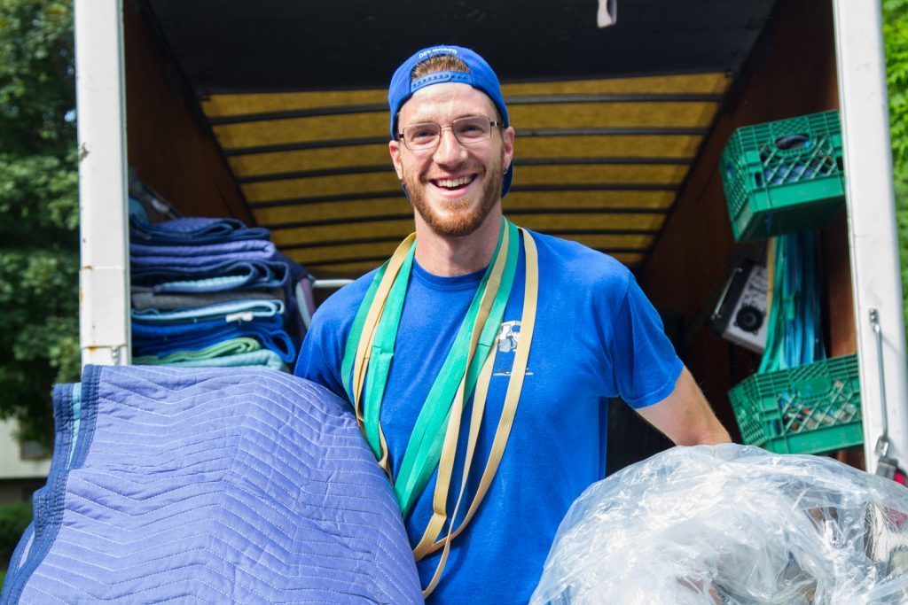 mover smiling with moving truck in background